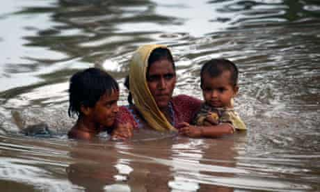 A Pakistani mother carries her children through flood water