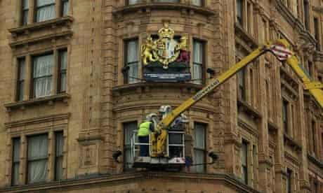 Workmen remove the royal crests from Harrods