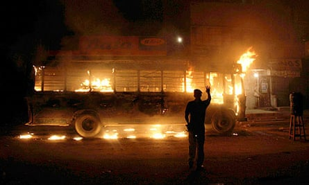 A policeman looks on at a bus torched by political activists in Karachi