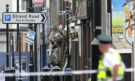 A police officer looks at damaged shops after a car bomb exploded outside a PSNI station in Derry.