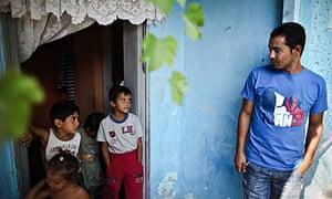 Romica Raducanu glances at his children outside his house in the village of Barbulesti, Romania.