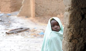 A girl stands by a derelict gold-processing plant in  Yargalm, in Nigeria's Zamfara state