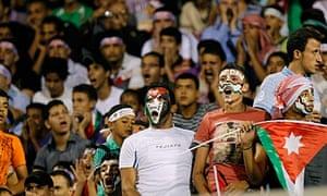 Football fans cheer Jordan against Kuwait at a match in Amman