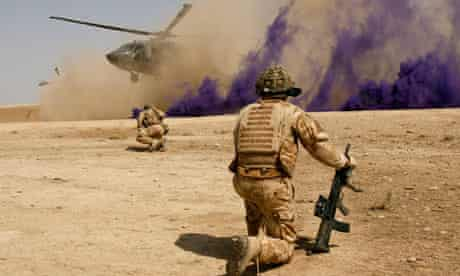 British soldiers cover themselves from dust as a helicopter lands at Malgeer in Helmand province.