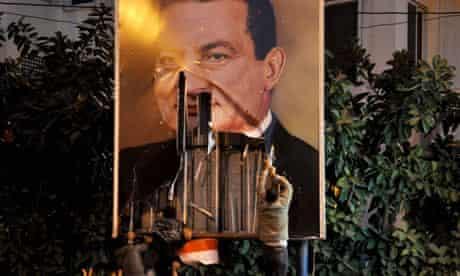 Egyptian demonstrators tear down a poster of President Hosni Mubarak in Alexandria.