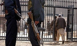 Afghan security police officers stand guard in front of the Pul-e Charkhi prison's gate in Kabul.