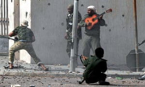 Libya's new regime forces fight as a comrade plays a guitar during a battle in Sirte