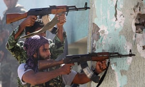Libyan National Transitional Council fighters fire at Gaddafi loyalists in battle for Sirte