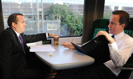 Primeminister David Cameron on a train with Liam Fox, who has resigned as defence secretary