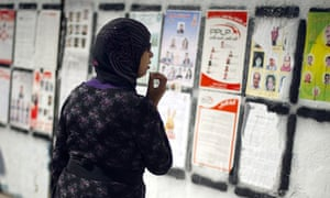 A Tunisian woman looks at a wall covered with posters of candidates ahead of the election