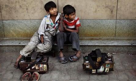 Shoeshine boys wait for customers in New Delhi, India