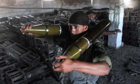 Libyan fighters carrying ammunition from