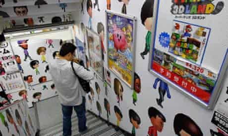 A man walks down the stairs covered with Nintendo Wii characters at an electronics retailer in Tokyo