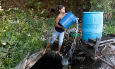 A woman collects water from a public well in San Cayetano, west Nicuragua