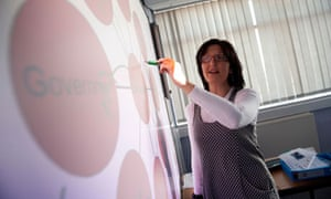 A woman doing a powerpoint presentation on a interactive  touch screen whiteboard