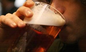 Man drinks pint of beer in British pub