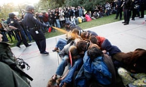 A police officer uses pepper spray at an occupy protest at University of California