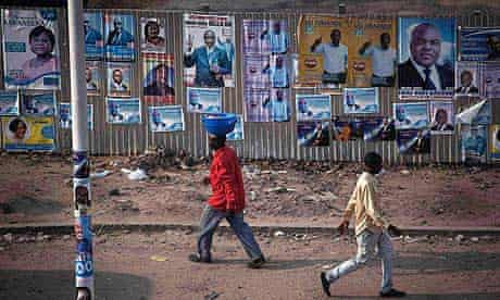 Pedestrians walk past election posters in Congo's capital Kinshasa