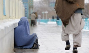 An Afghan woman sits on the ground as she begs next to Hazrat-e Ali shrine in Mazar-i Sharif on