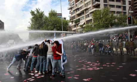 Demonstrators are hit by a jet of water during a rally in Santiago, Chile