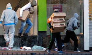 Looters carry boxes out of a shop in Birmingham