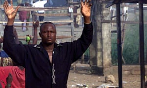 Nigerian civillian raises hands to soldiers