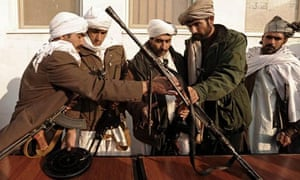 Taliban fighters arrange their weapons after joining Afghan government forces at a ceremony in Herat