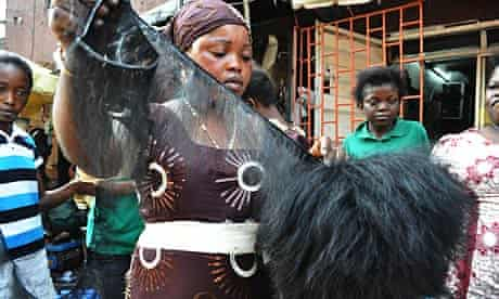 A vendor displays some hair extensions in a Lagos market.