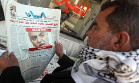 An Iraqi man looks at a newspaper featuring a front page picture of Tareq al-Hashemi