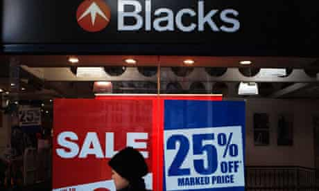 A pedestrian walks past retailer Blacks