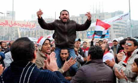 Egyptian anti government protesters shout slogans as they continue their presence in Tahrir square