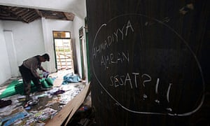 A policeman collects evidence from a house where Ahmadiyah members were attacked