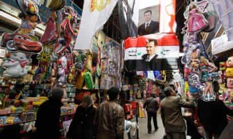 Images of Syria's president, Bashar al-Assad, hang in a Damascus market.