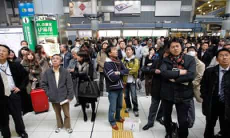 Train passengers wait at Tokyo's Shinagawa station for information on halted train services