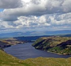 Haweswater beneath an emal-blue sky and billowing clouds in the aftermath of winter.