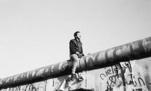 A young man sits atop the Berlin Wall and howls for joy, 1989
