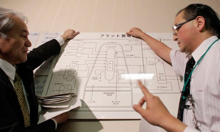 Tokyo Electric Power officials hold a diagram of the plant at the disaster center in Fukushima.