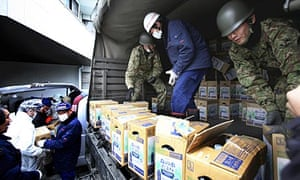 Japanese Self Defence Force members unload boxes of drinking water in Litate, Fukushima prefecture.