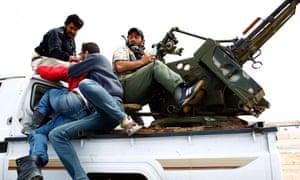 Libyan rebels flee artillery fire on the road between Ajdabiya and Brega