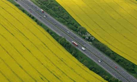The M4 motorway surrounded by rapeseed fields at Tormarton, near Tetbury, England.
