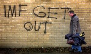 A man carrying his tools walks near a graffiti in South Dublin