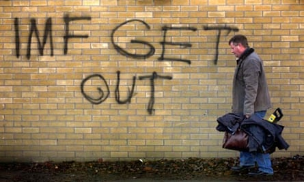 A man carrying his tools walks near a graffiti in South Dublin