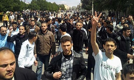 Syrian anti-government protesters march in Homs.