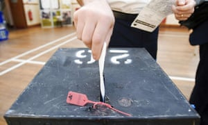 A voter places his voting card into a ballot box at a polling station in Wandsworth, south London