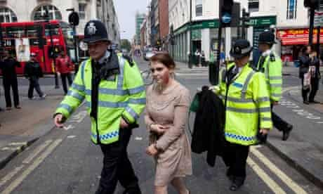 Police detain a woman dressed as a zombie