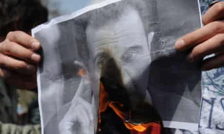 A protestor burns a portrait of Syrian president