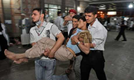 Anti-government protesters carry a wounded demonstrator to a field hospital