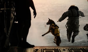 A US army soldier and his dog leap from a helicopter