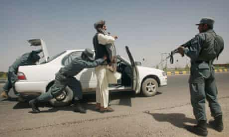 Afghan police search a car at a checkpost in Herat
