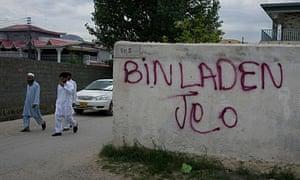 "Pakistanis walk past graffiti translated as ""long live Bin Laden"" in Abbottabad."